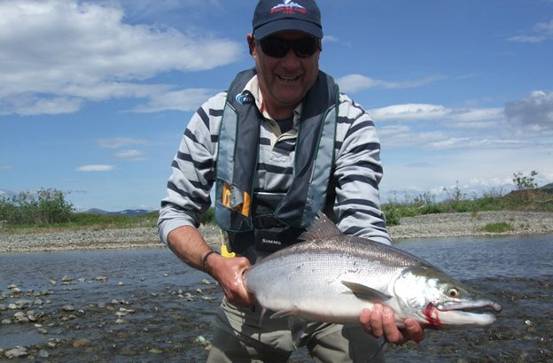 Lord Bowling holding one of his many salmon fly fishing in alaska