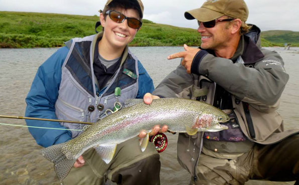 happy guide and customer with a big rainbow trout at no see um lodge alaska