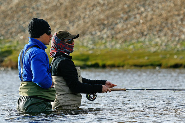 customer and guide standing in river fly fishing for sea trout