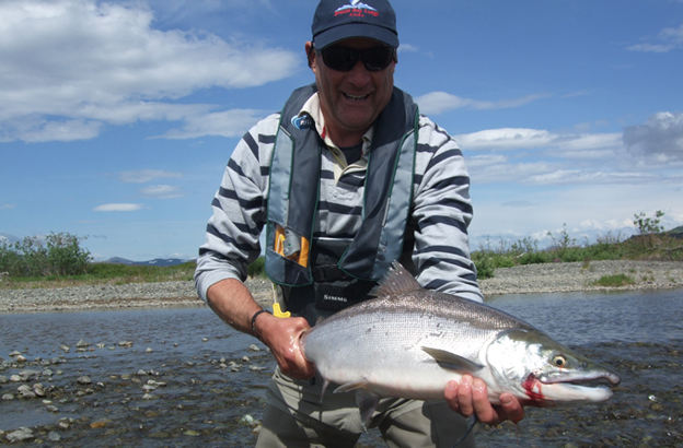 customer holding a fresh sockeye salmon from Alaska Hosted Salmon Fishing Reports