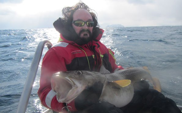 a man with black hair holding a big Cod Norway fishing report