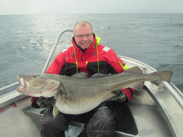 A man holding his very large Skrei Cod from Soroya Norway Fishing Report