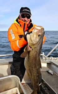 Old man holding a big Cod Norway fishing report