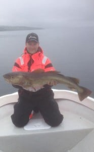 Man on his knees holding a Cod Fishing Report Norway