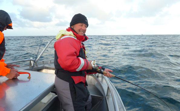 A very happy man fishing report Norway catching Cod