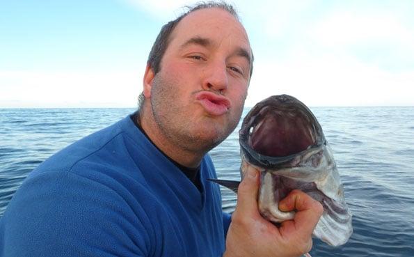 Man posing with small coalfish fishing report Norway
