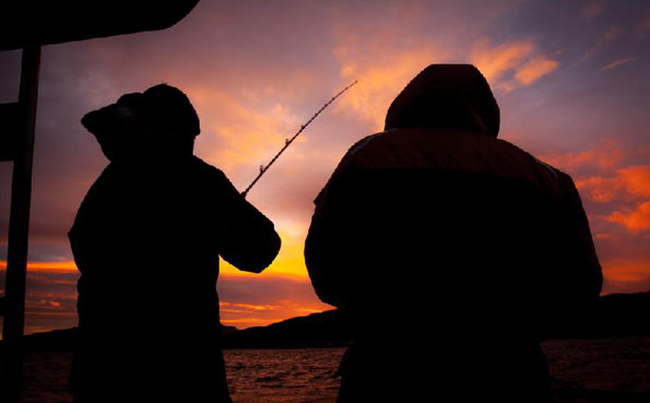 Two fishermen in a sunset shot Norway fishing report