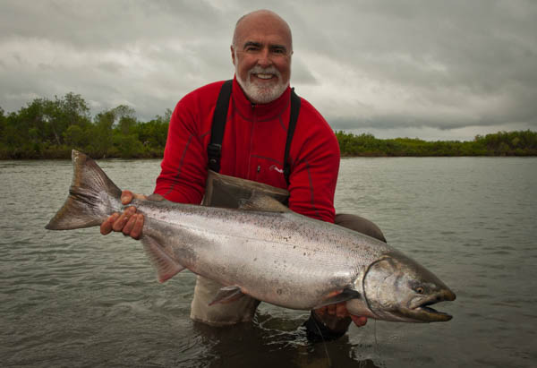 a customers holding a cracking king salmon from alaska west camp