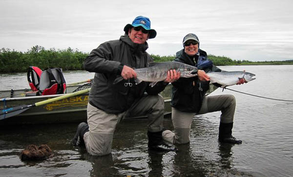 a couple looking happy with their brace of salmon caught fly fishing at alaska west fly fishing camp