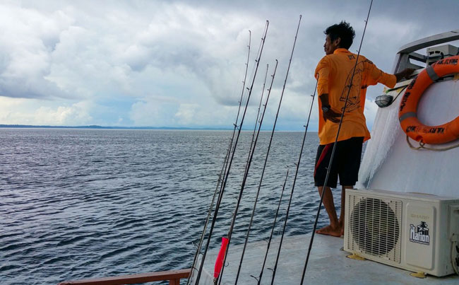 Guide standing looking for fish Indonesia Fishing Report