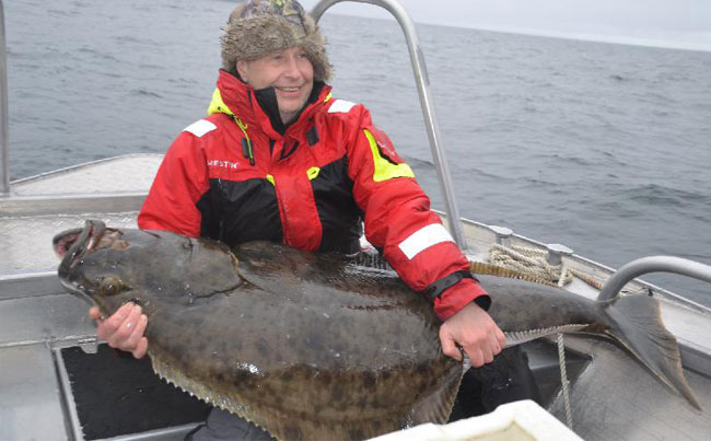 Man holding a massive Halibut for Norway Fishing Report