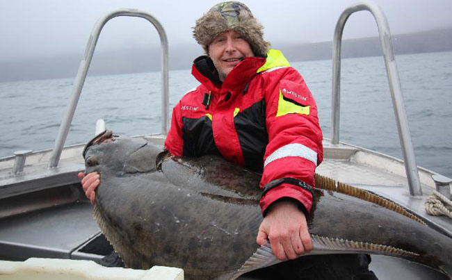 Man holding a huge Halibut caught for our Norway Fishing Report