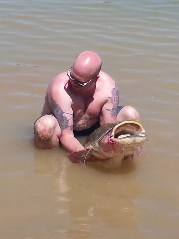 Holding a huge catfish in the water Spain Fishing Report