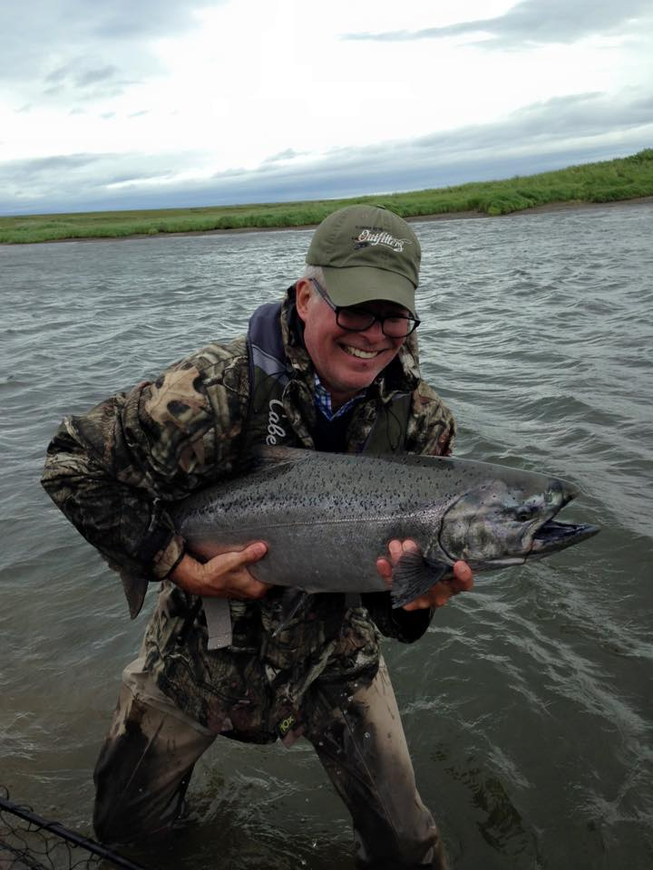 customer tries to hold onto his big king chinook salmon caught fly fishing