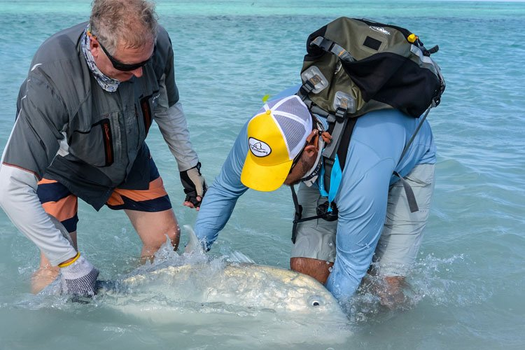 customer and guide release a nice GT caught fly fishing on Farquhar seychelles