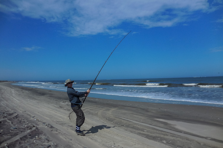 Angler With Rod Bent On The Beach