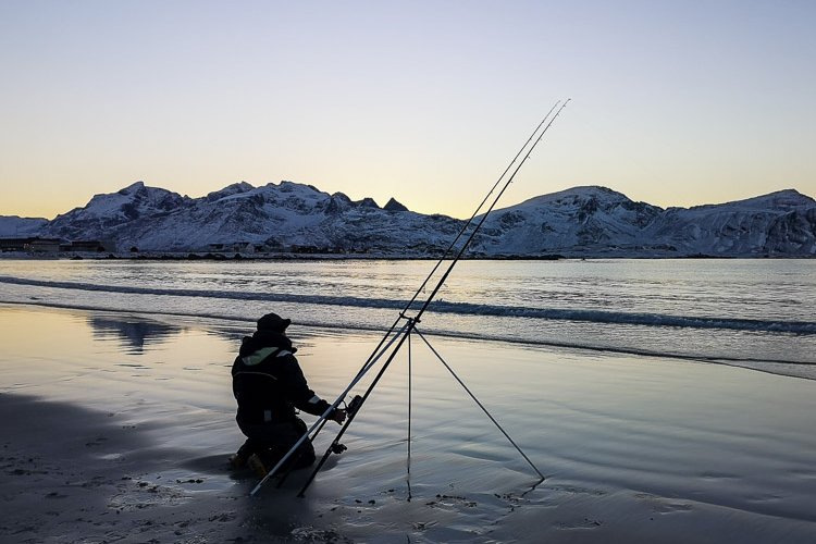 Angler setting up his rod on the beach